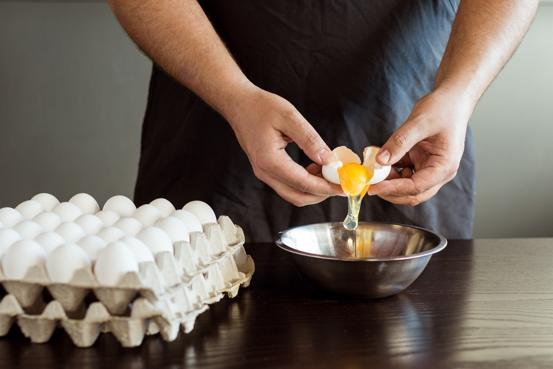 Chef cracks eggs at Mici Handcrafted Italian in Denver, CO.