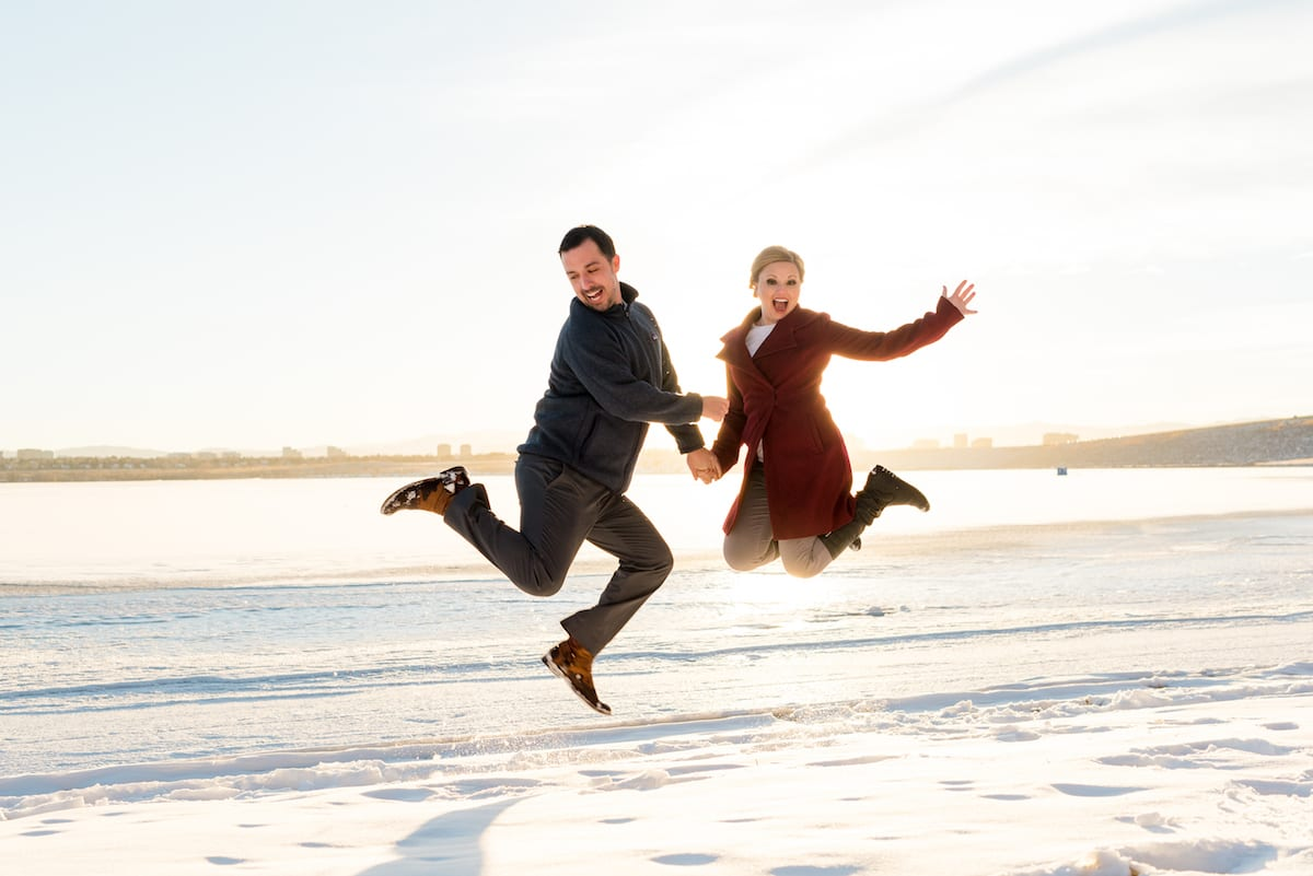 cherry creek state park engagement photos, a couple jumps in the snow.