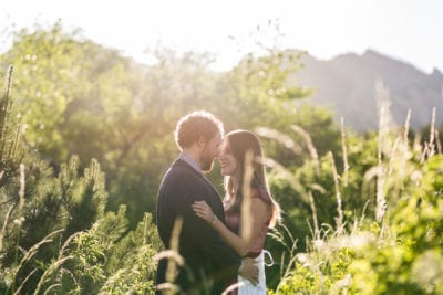 A couple looks into each other's eyes, standing in a mountain landscape