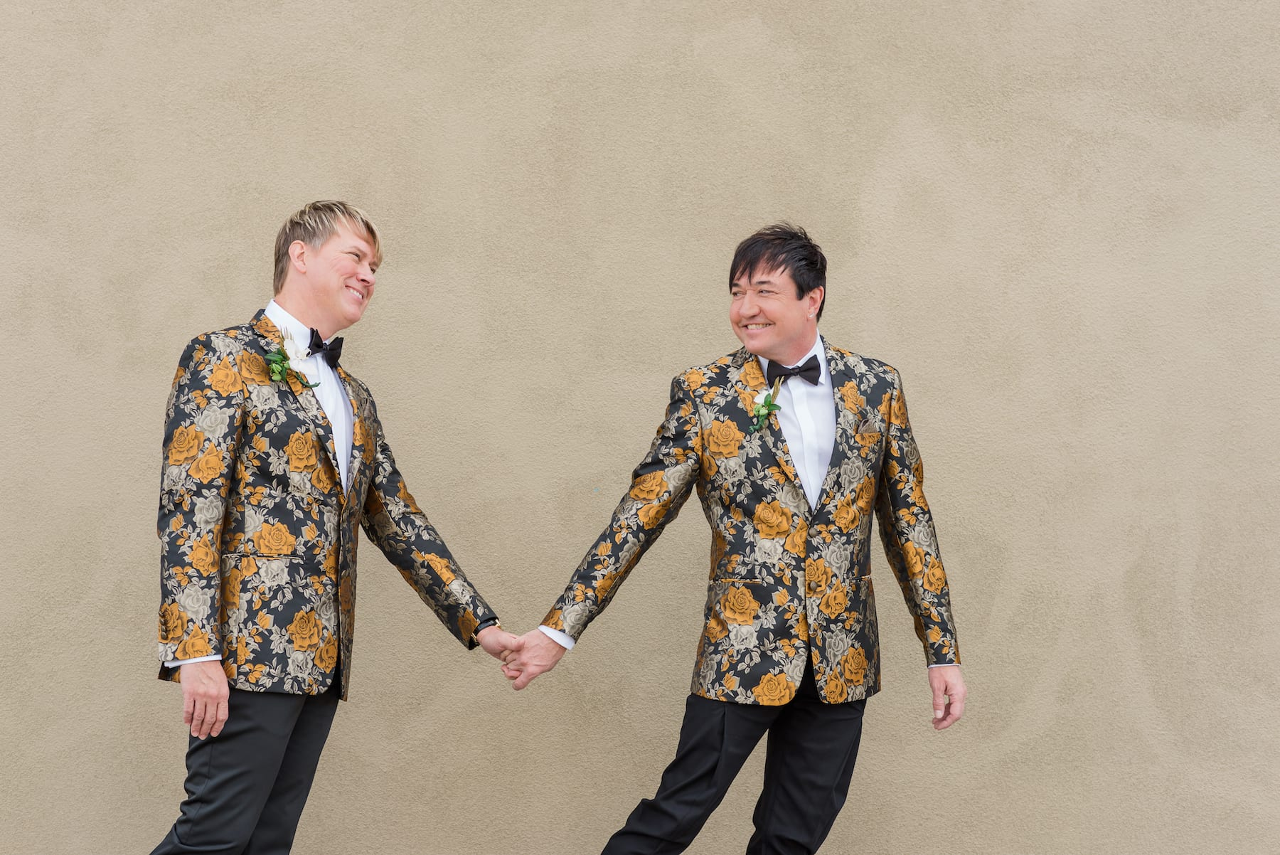 A colorful-suit-wearing couple holds hands and smiles in front of a tan backdrop