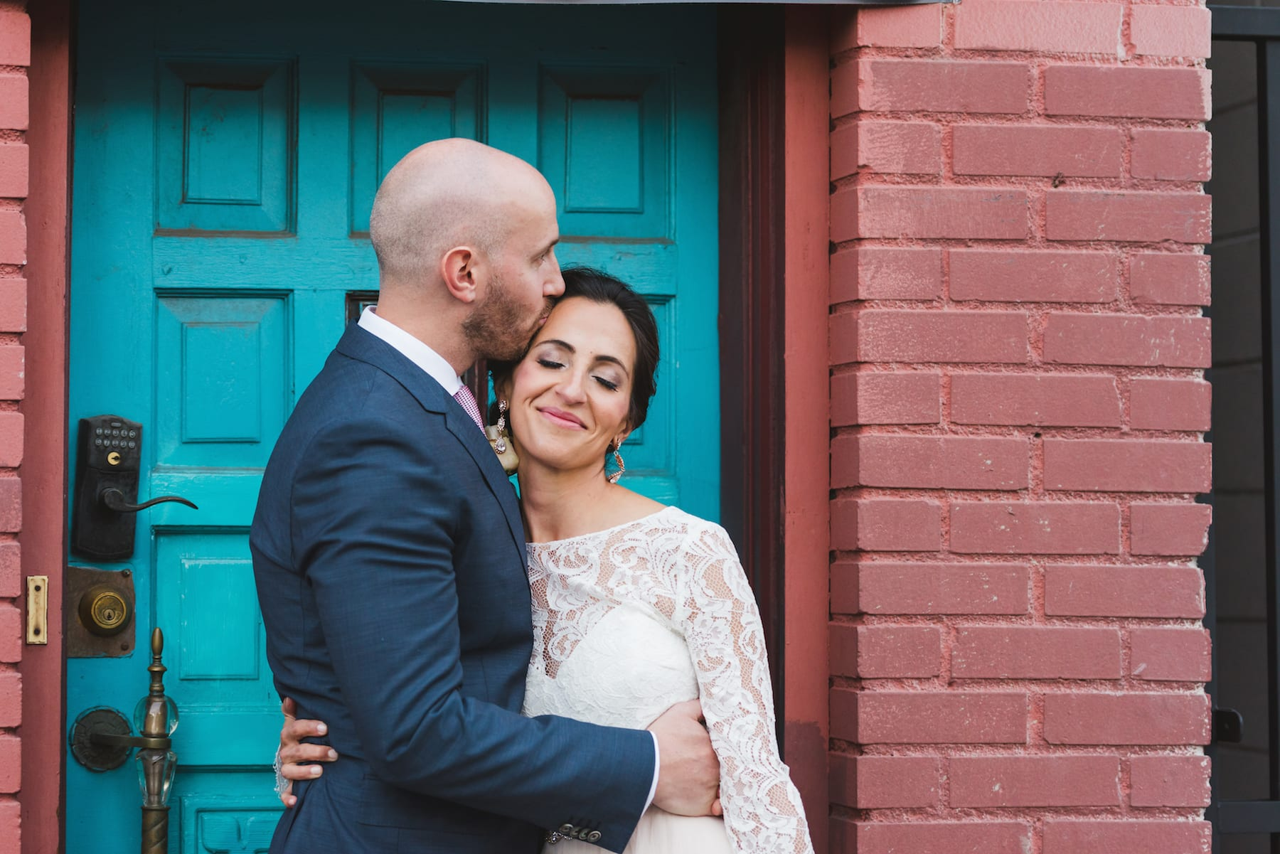 A couple embraces one another in front of a blue doorway