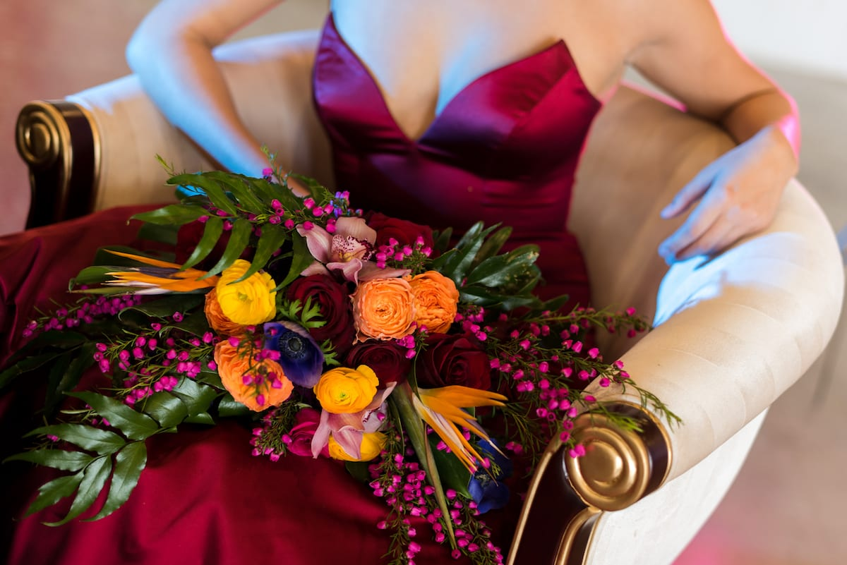 bride in ruby dress with colorful bouquet