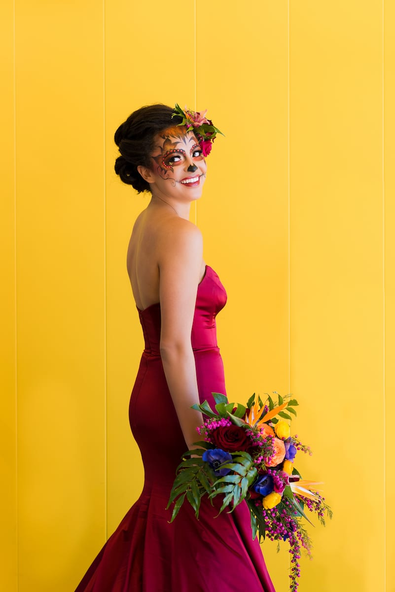 bride poses with colorful bouquet and candy skull makeup