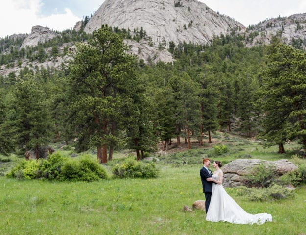 bride and groom in front of a mountain