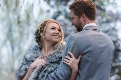 Bride looks lovingly at groom in winter shawl