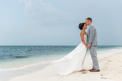 Groom kisses bride's forehead on beach