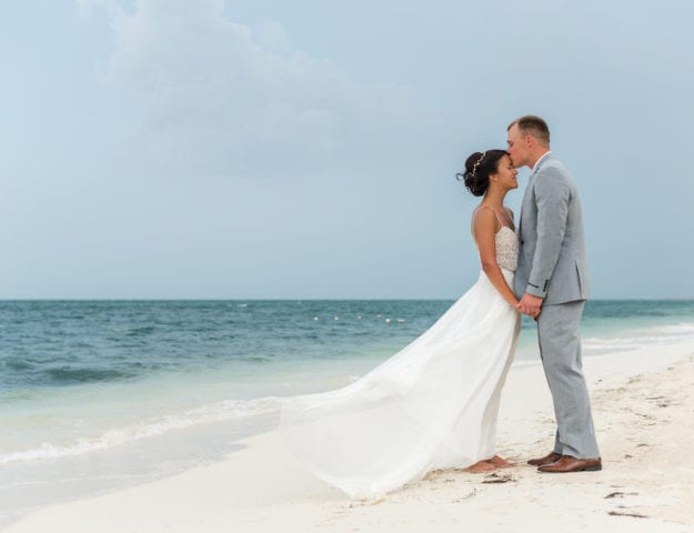 Groom kisses bride's forehead on beach