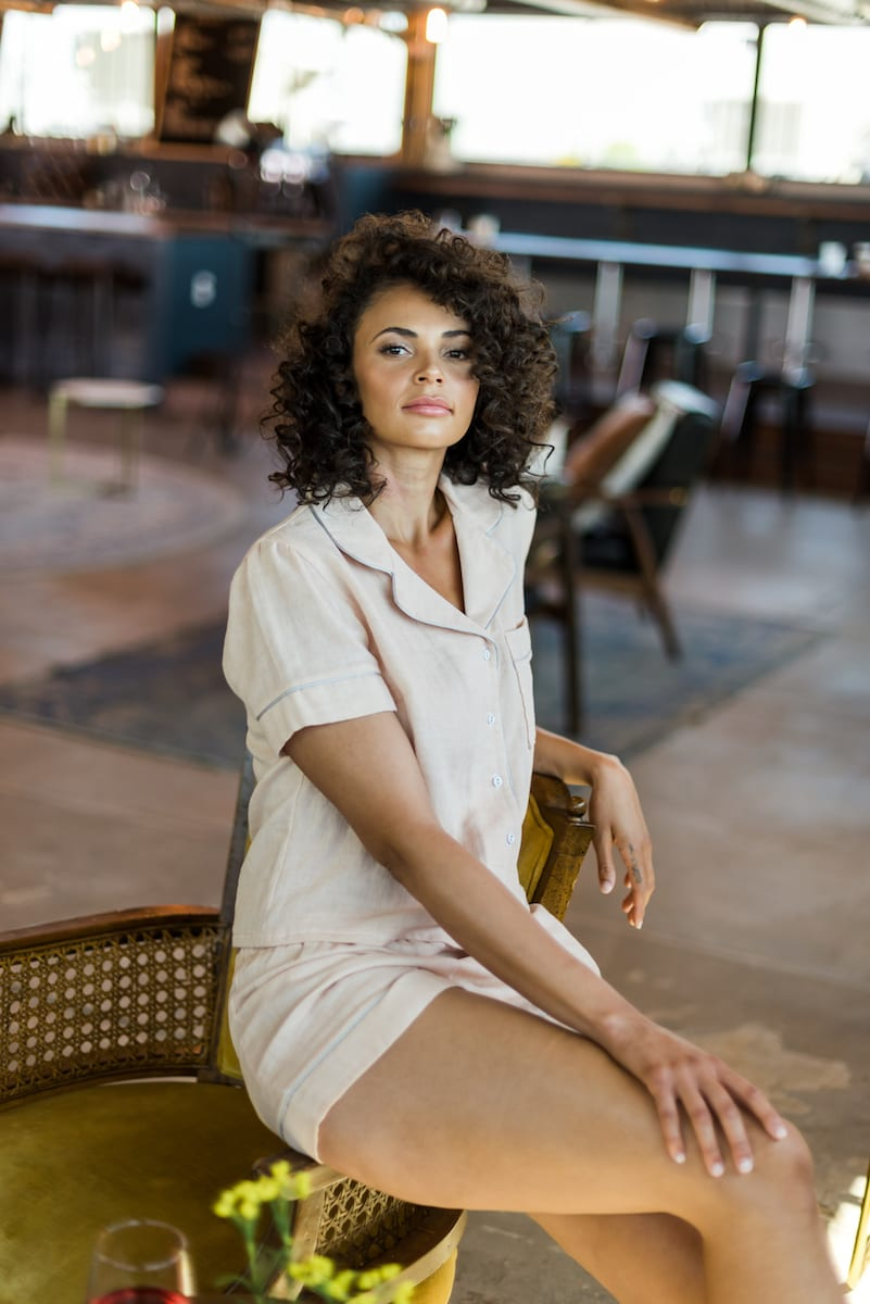 Model in tan pajama top sits on a bench