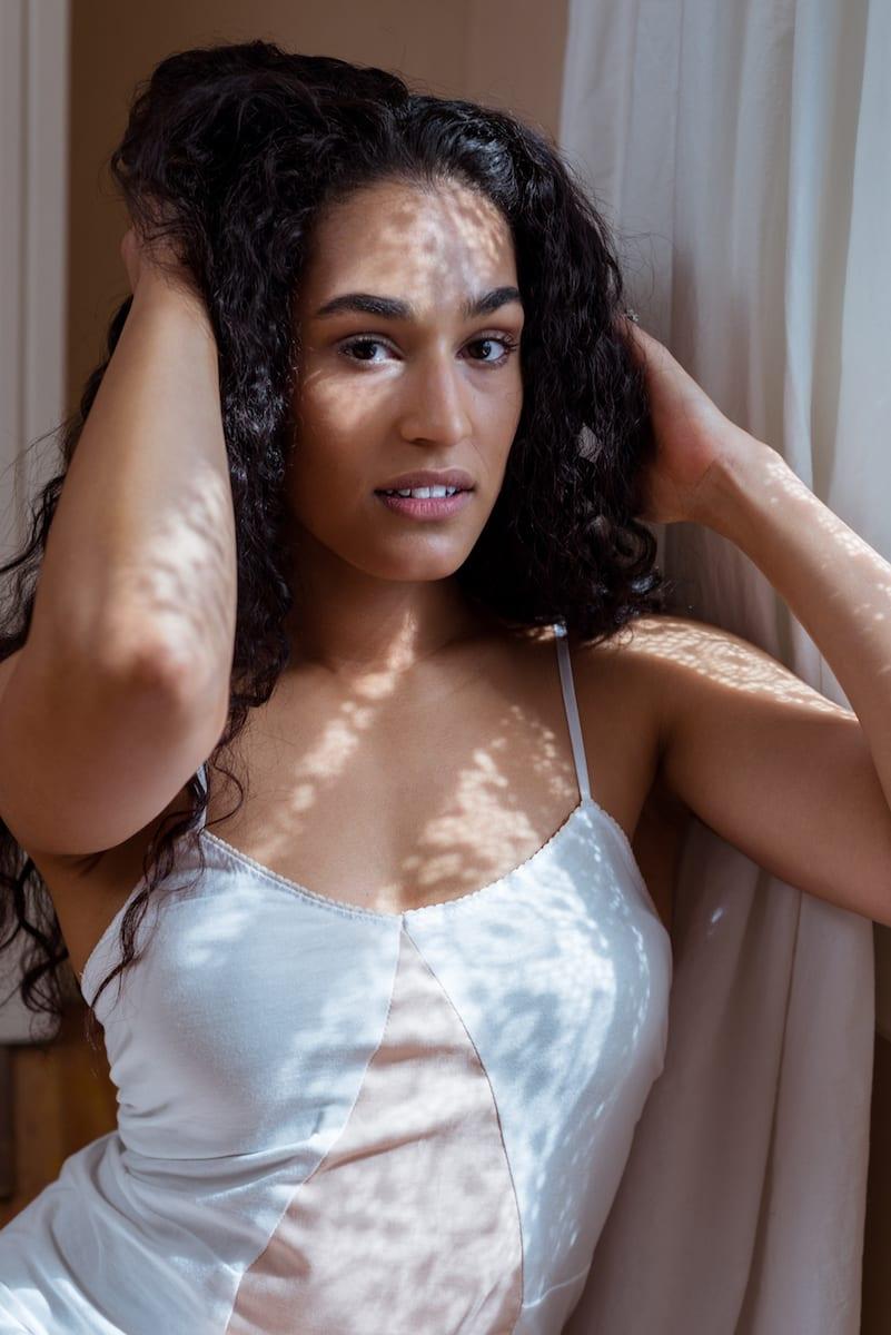 Model in white lingerie tossles hair