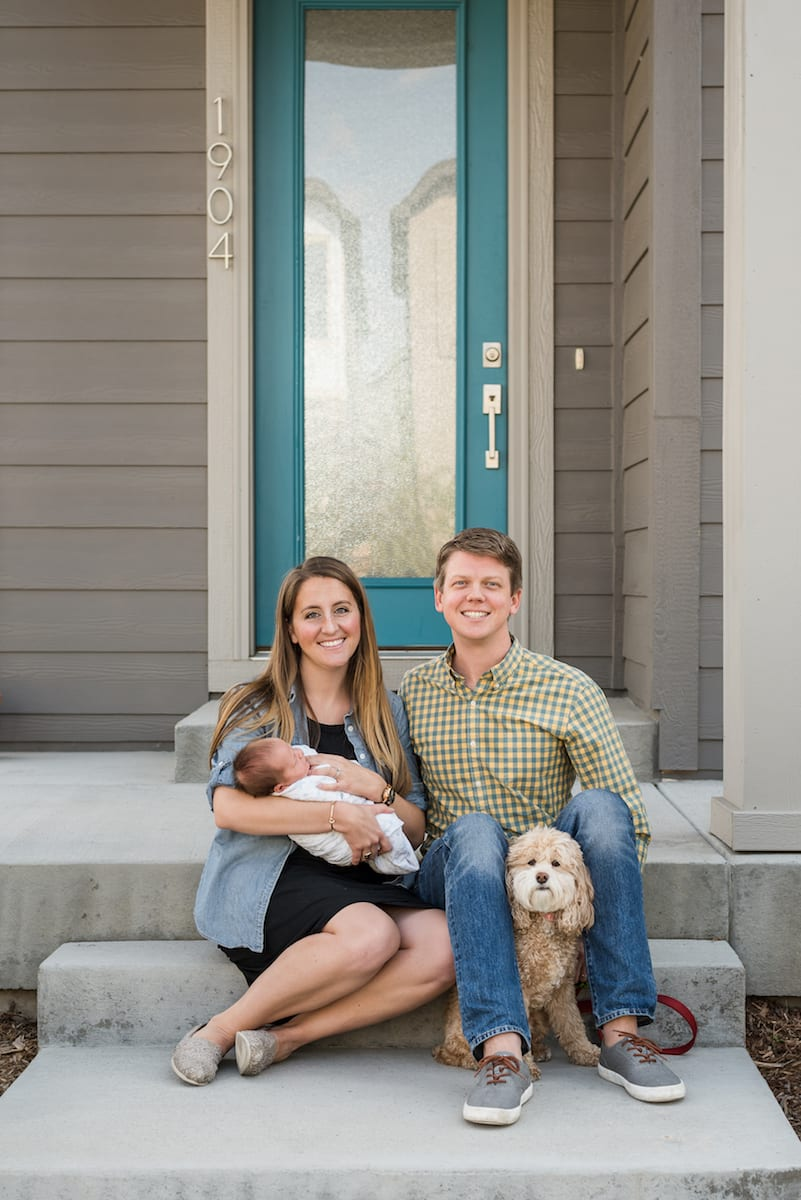 Parents holding newborn with dog in photo