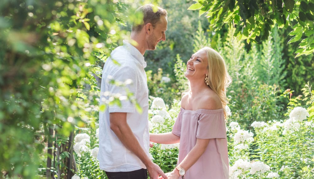 Man holds woman's hands amidst foliage at Botanic Gardens
