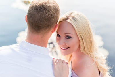 Woman looks over man's shoulder, showing off engagement ring