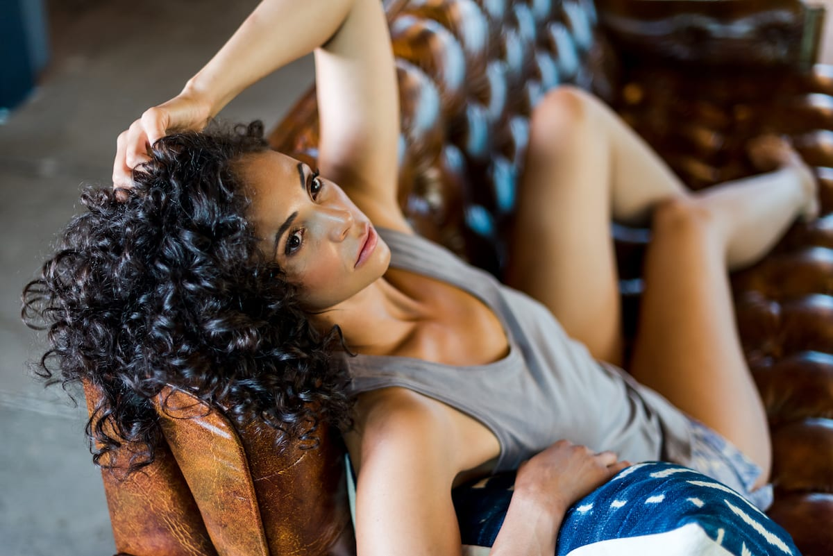 model in grey tank top lays on couch with one arm over head