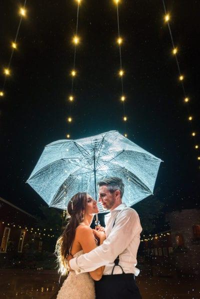 Bride and groom stand under translucent umbrella underneath string lights