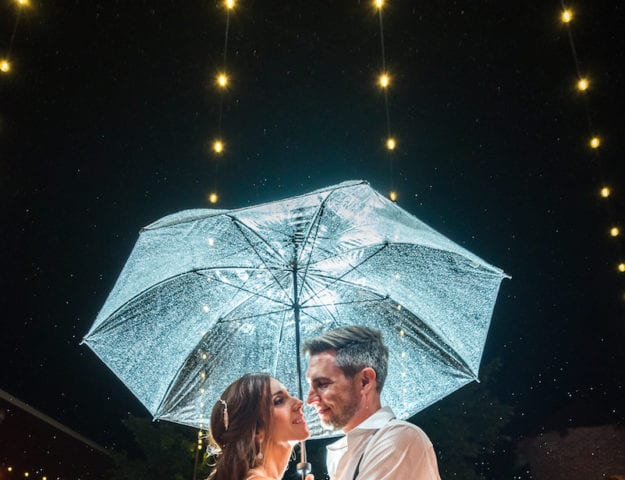 Bride and groom stand under translucent umbrella underneath string lights