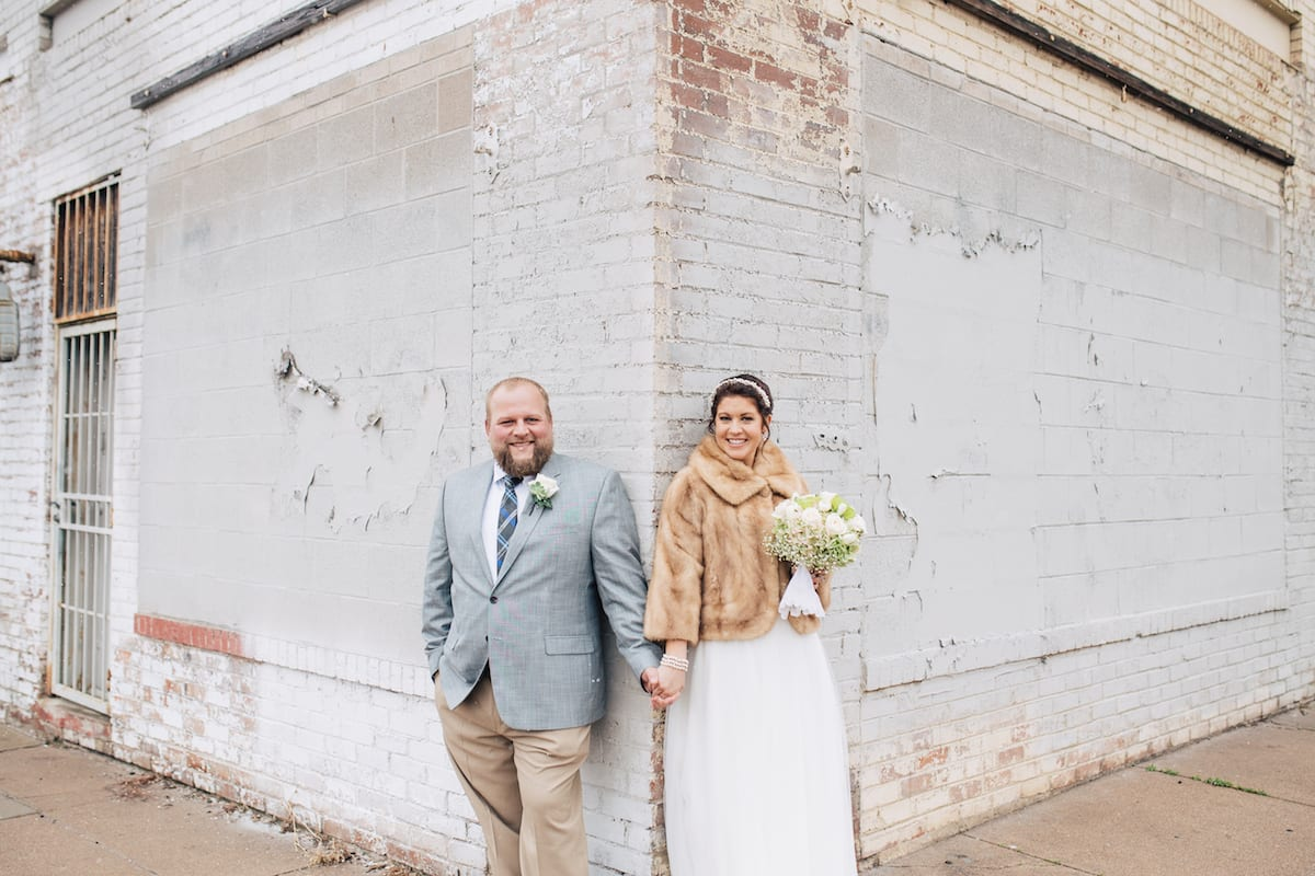 keep warm during a winter wedding   Wedding Photography   From the Hip Photo   Bride and groom stand on brick wall. Bride is wearing a fur jacket