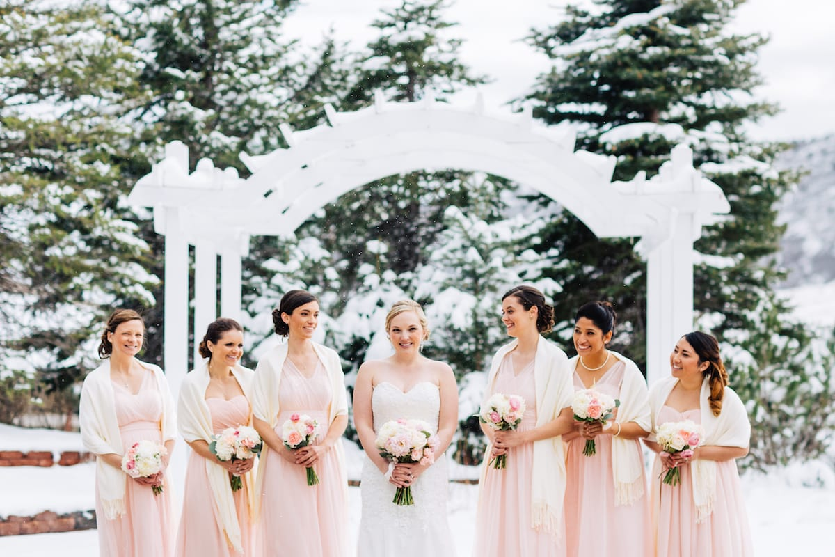 keep warm during a winter wedding   Wedding Photography   From the Hip Photo   bride stands surrounded by bridesmaids in winter shawls