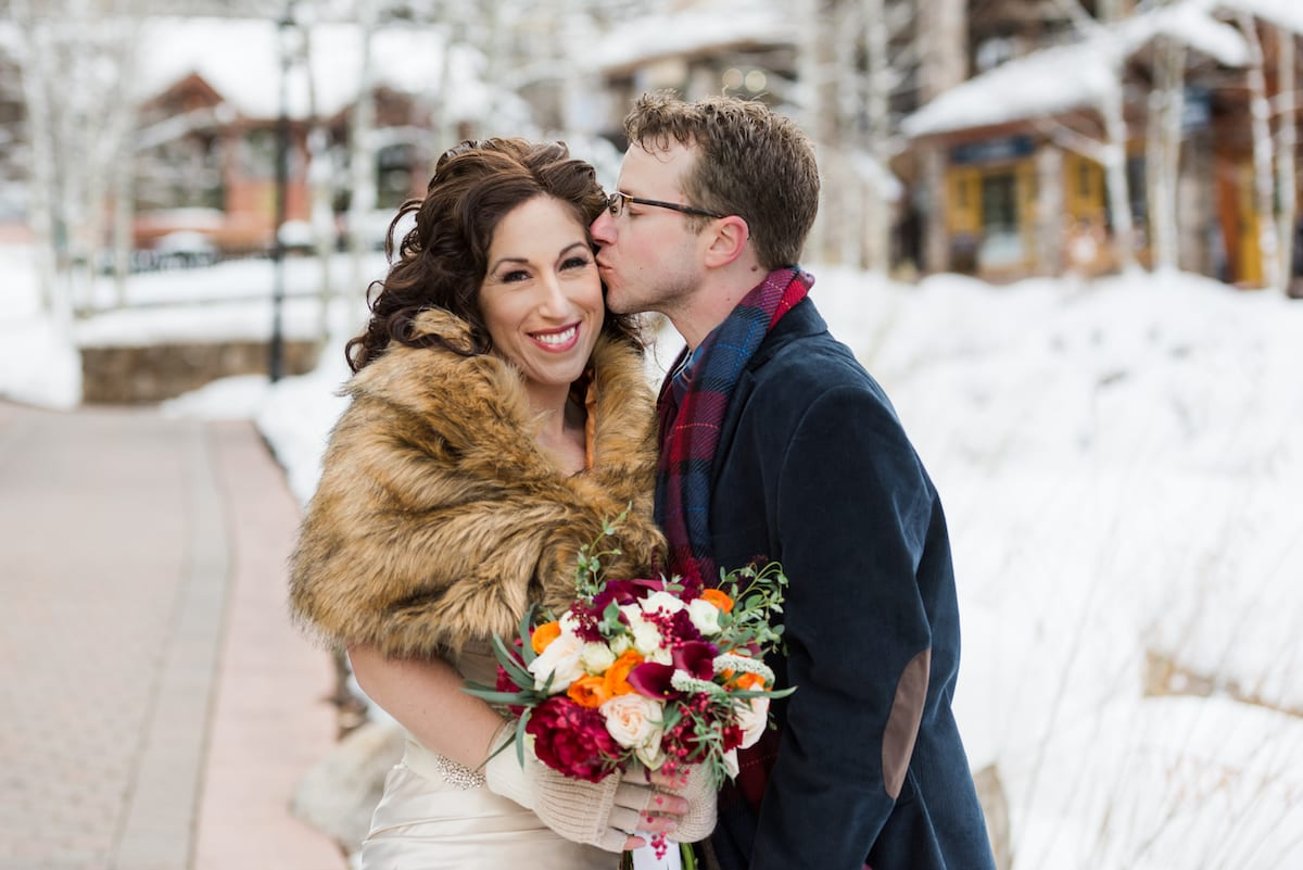 keep warm during a winter wedding   Wedding Photography   From the Hip Photo   bride holds a winter bouquet of flowers, receives a kiss on the cheek from groom, and wears a winter shawl