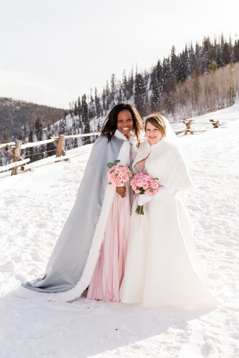 keep warm during a winter wedding | Wedding Photography | From the Hip Photo | bride and bridesmaid wear winter cloaks on snowy mountainside