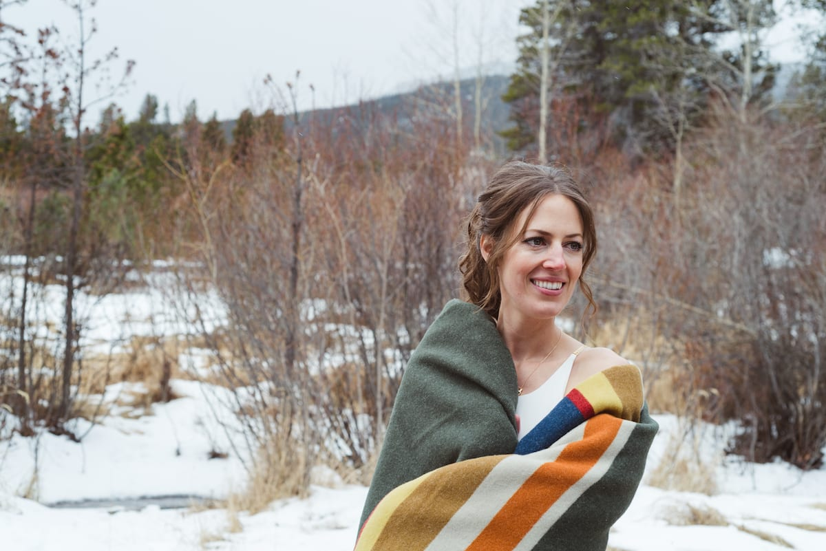 keep warm during a winter wedding | Wedding Photography | From the Hip Photo | Bride wrapped in an orange and grey blanket stands in a snowy field