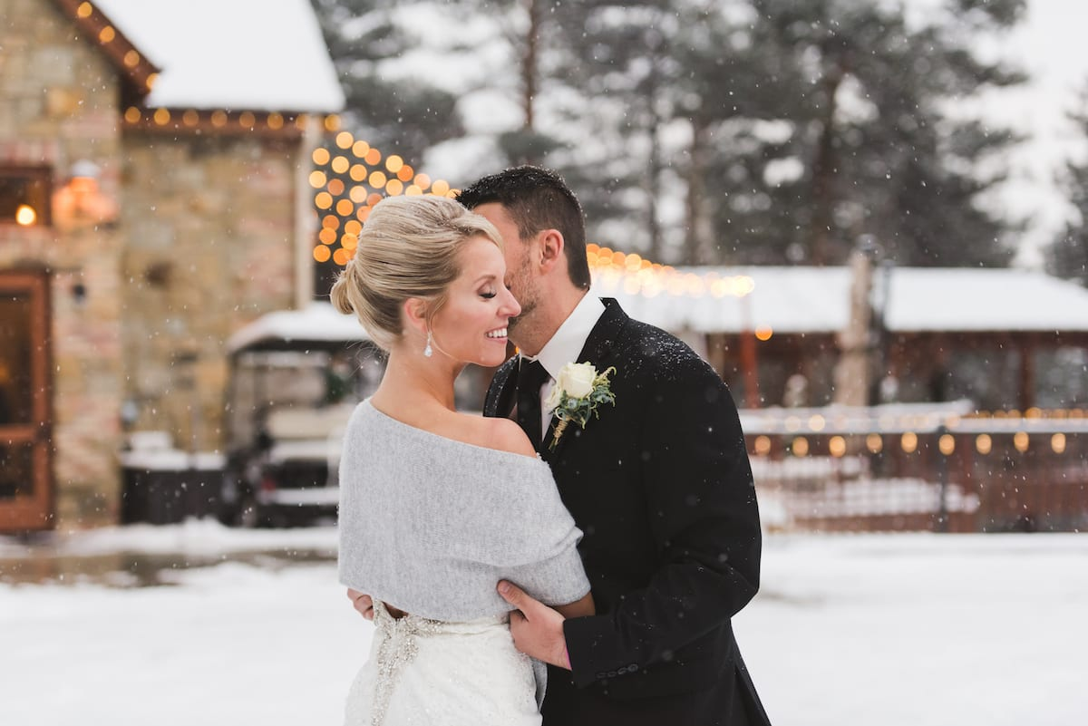 keep warm during a winter wedding   Wedding Photography   From the Hip Photo   Bride wears a light shawl while receiving a kiss on the cheek from groom