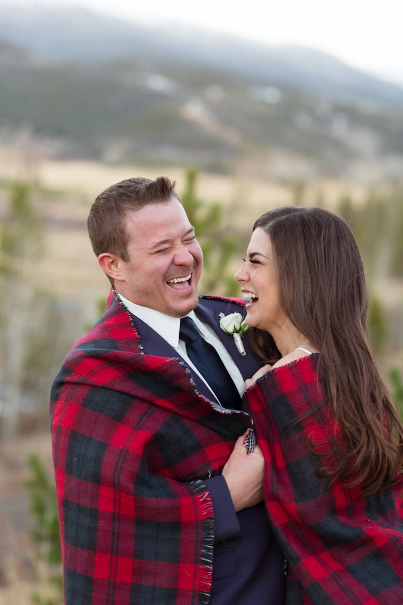 keep warm during a winter wedding   Wedding Photography   From the Hip Photo   bride and groom huddle together in a red flannel blanket while laughing