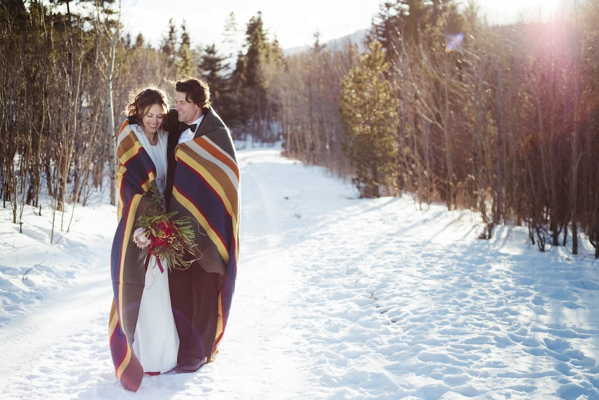 keep warm during a winter wedding   Wedding Photography   From the Hip Photo   bride and groom walk through a snowy alley wrapped in a large blanket