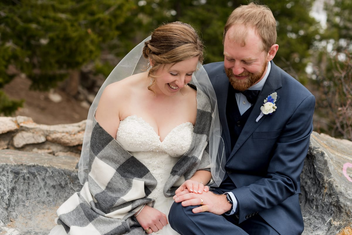 keep warm during a winter wedding | Wedding Photography | From the Hip Photo | Bride sits with groom wrapped in a gray flannel blanket