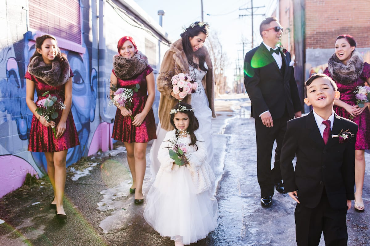 keep warm during a winter wedding | Wedding Photography | From the Hip Photo | bride in a fur coat walks down an alley. Her bridesmaids are wearing red dresses with fur scarves. Her groom and a ring boy stand by